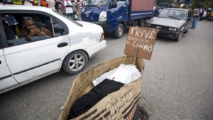 """A man takes pictures from a taxi of a fake coffin that represents Provisional President Jocelerme Privert, with a sign that reads Creole """"Privert resign or die"""" in Port-au-Prince."""